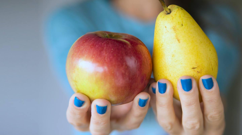 Low-FODMAP-Diät: Frau mit blau lakierten Fingernägeln hält einen Apfel und eine Birne in den Händen.