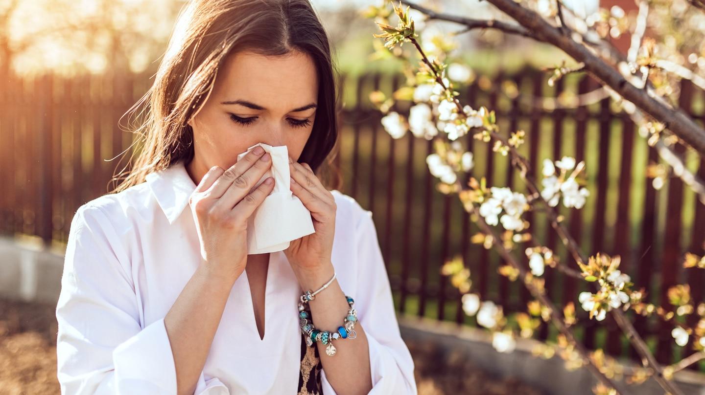 Heuschnupfen: Junge Frau im Garten putzt sich die Nase. Hinter ihr ein Blütenzweig.