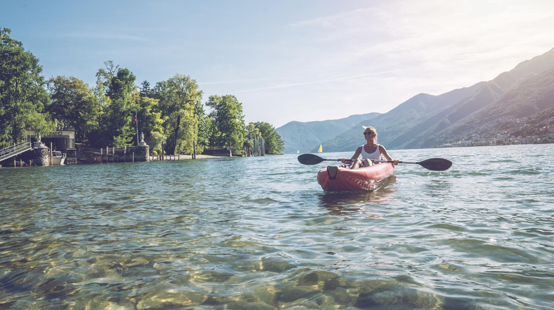 Wassersportarten im Check: Frau paddelt mit einem aufblasbaren Kanu über einen See in den Alpen.